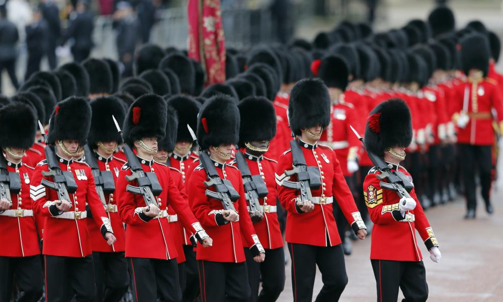 Soldiers parade as the Queen travels in a carriage from Buckingham Palace towards the Houses of Parliament.