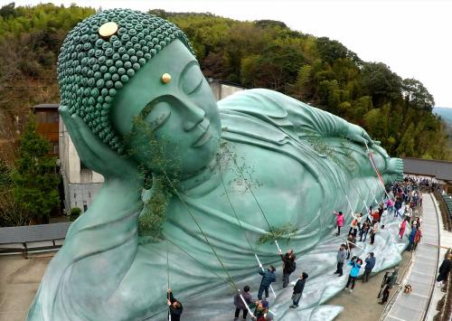 Parishioners clean up the Reclining Buddha with bamboo branches at Nanzoin temple in Fukuoka, Japan. Some 200 monks and visitors take part in the annual year-end dusting of the 41-metre-long statue.