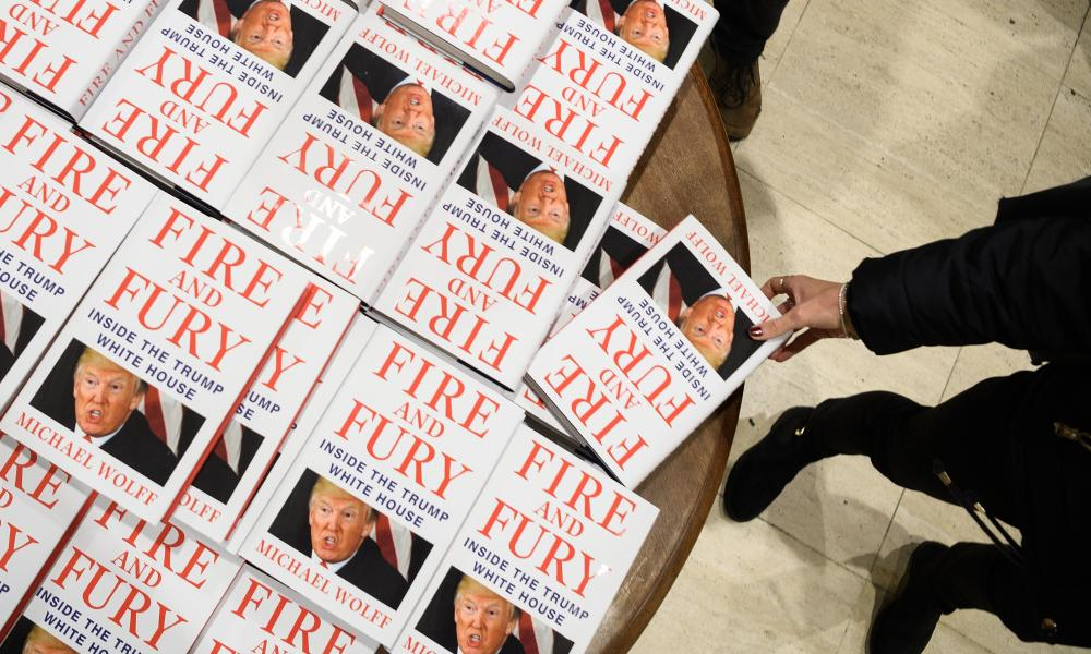 A customer takes a copy of Fire and Fury from a table in Waterstones Piccadilly in London.