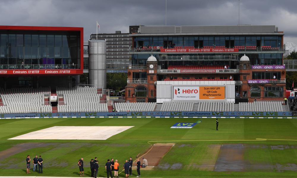 Groundstaff stand around on the outfield at Old Trafford after fifth Test called off
