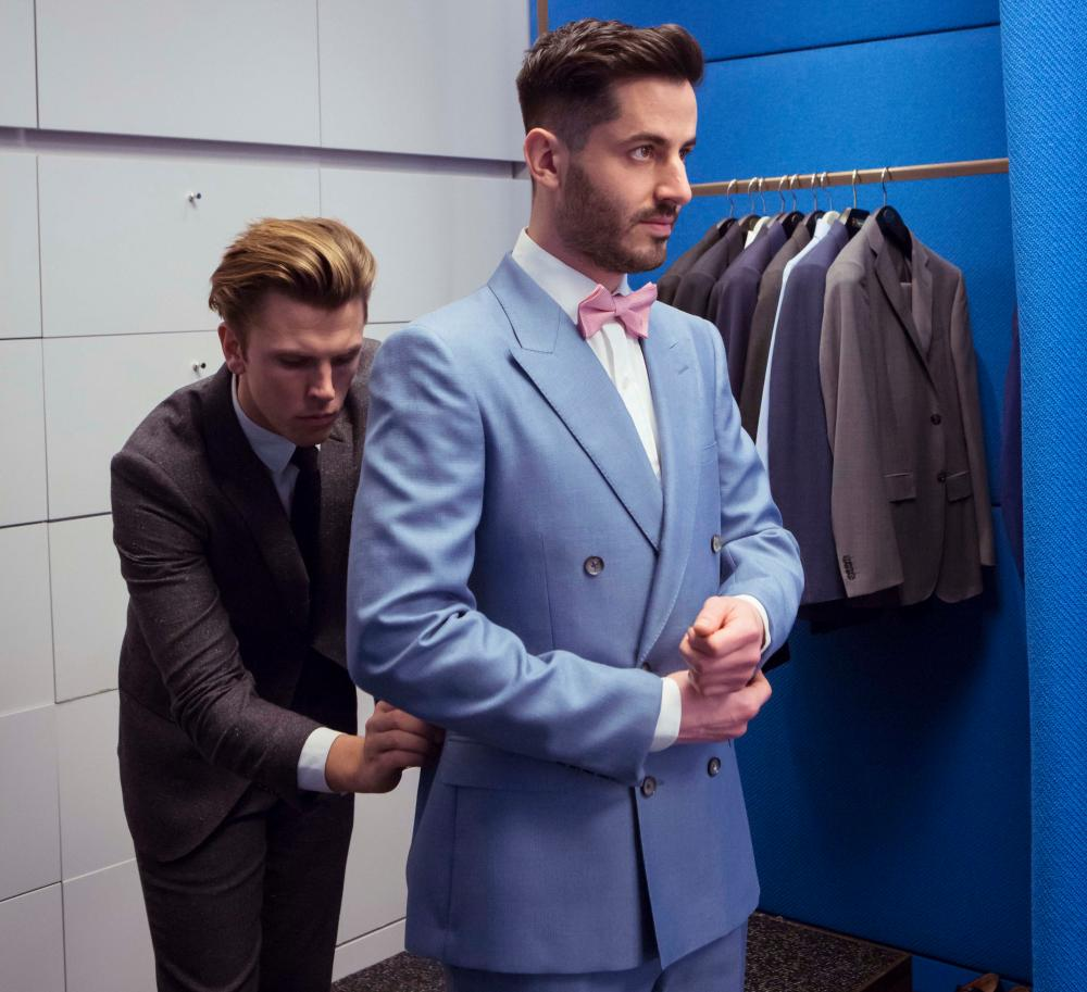 Daniel Masoliver trying on an Alexander McQueen suit, with Selfridges' personal shopper Kristian Bayliss behind him