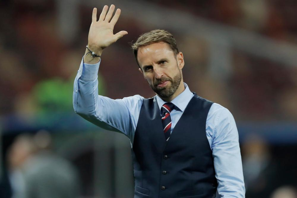 Gareth Southgate waves to the England fans as they chant his name over an hour after the final whistle of England's semi-final defeat to Croatia.