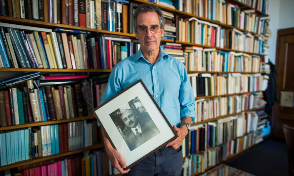 In his Columbia University office, Mark Mazower holds a photograph of his grandfather Max.