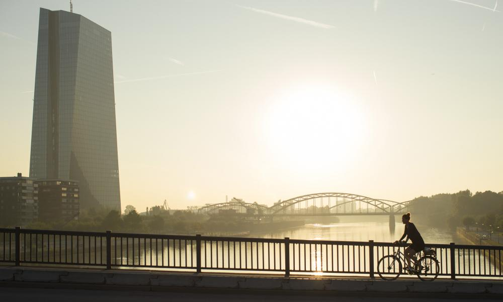 A cyclist rides across a bridge as the skyscraper headquarters of the European Central Bank.