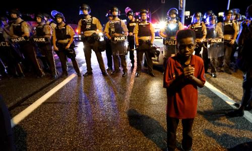 Amarion Allen, 11-years-old stands in front of a police line shortly before shots were fired in a police-officer involved shooting in Ferguson, Missouri August 9, 2015.  Two people were shot in the midst of a late-night confrontation between riot police and protesters, after a day of peaceful events commemorating the fatal shooting of Michael Brown by a white officer one year ago.  REUTERS/Rick Wilking