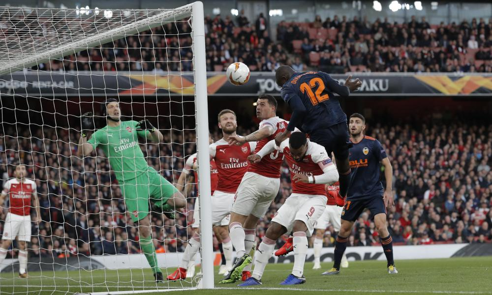 Mouctar Diakhaby of Valencia outjumps Alexandre Lacazette and Granit Xhaka of Arsenal as he scores his team's first goal past Petr Cech.