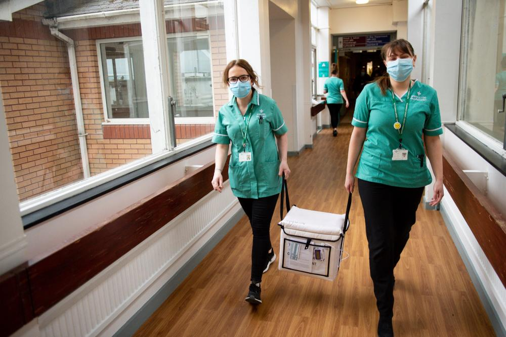 Pharmacists carrying a cooler containing the Moderna vaccine at the West Wales General Hospital in Carmarthen this morning.