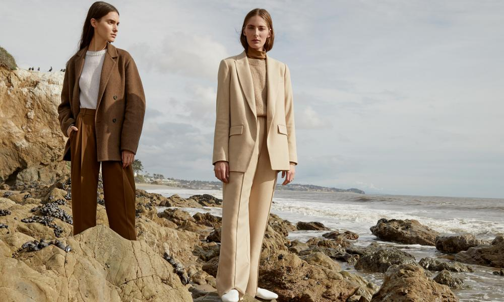 Two models on rocks by the sea in Vince's AW19 collection.