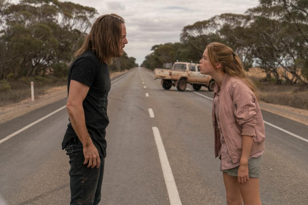a man and a teenage girl stand in the middle of a road, arguing