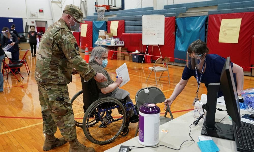 A member of the national guard transports a patient to receive the Covid-19 vaccine in Martinsburg, West Virginia, in March. An impressive early vaccination effort has not been sustained.