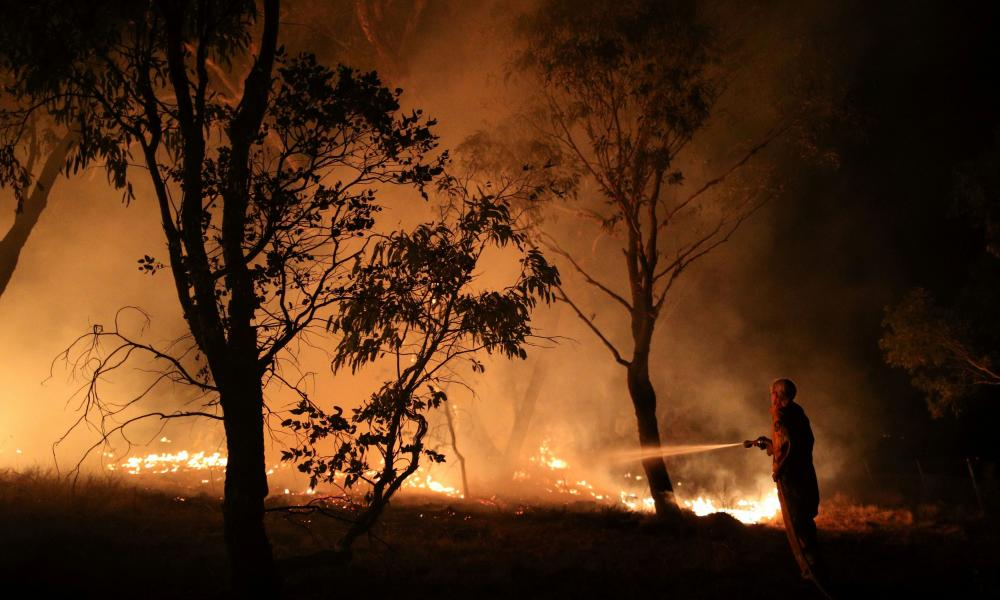 A firefighter from a local brigade works to extinguish flames after a bushfire burnt through the area in Bredbo, New South Wales, Australia.
