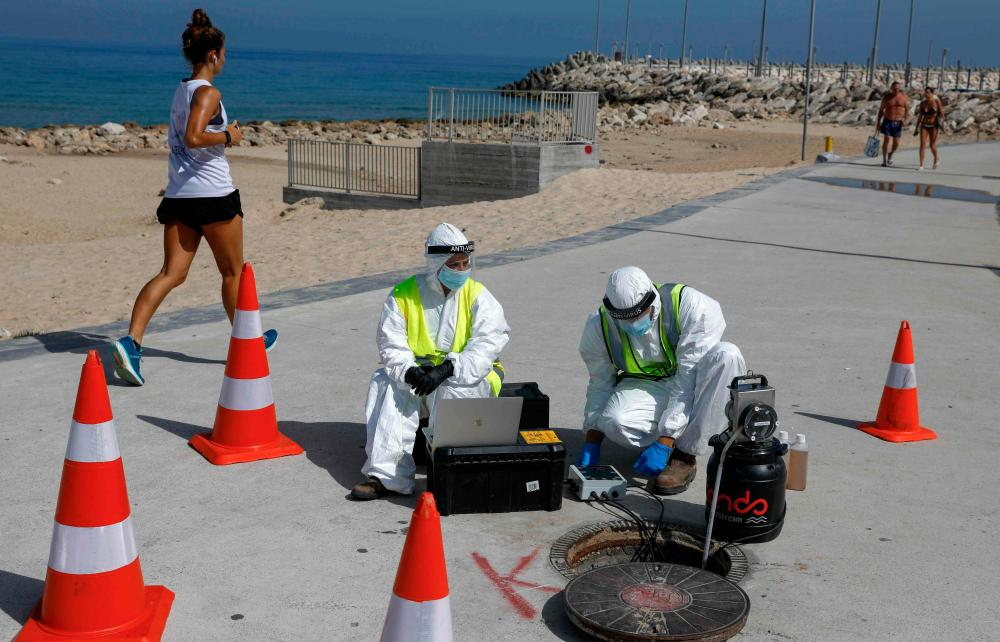 Technicians from Israeli firm Kando extract sewage samples from a manhole in the southern coastal Israeli city of Ashkelon.