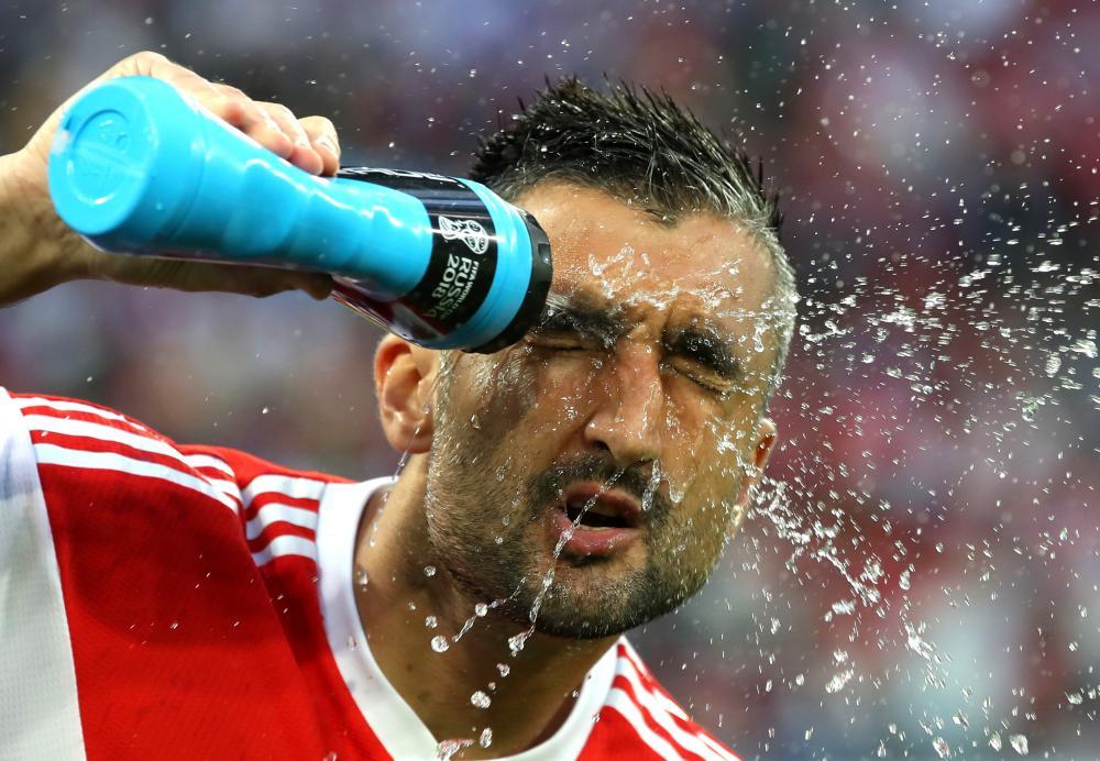 Alexander Samedov of Russia sprays water to refresh prior to the match.