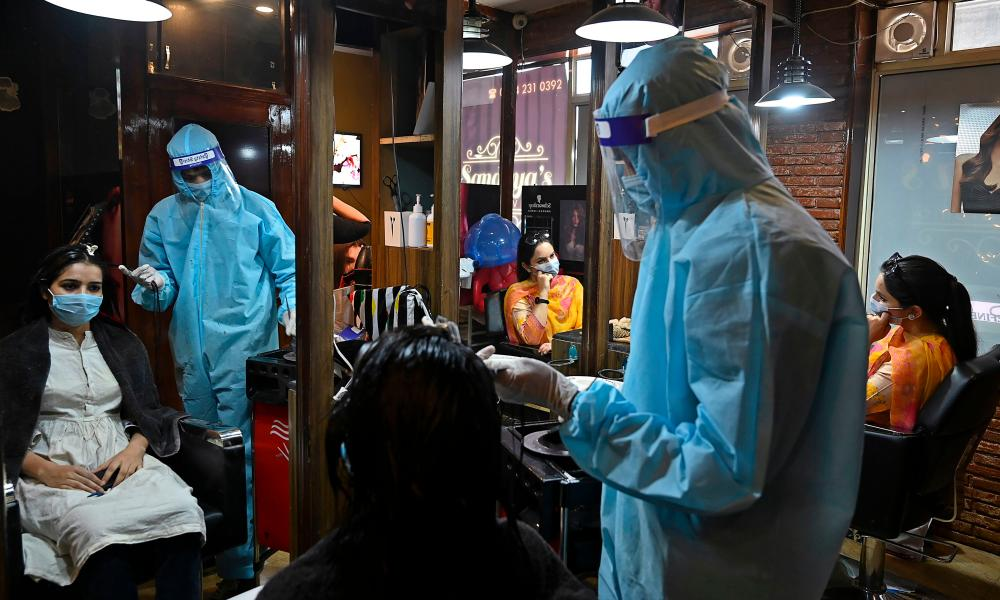 A hairdresser wearing personal protective equipment attends a customer at a hair salon in Srinagar, India.
