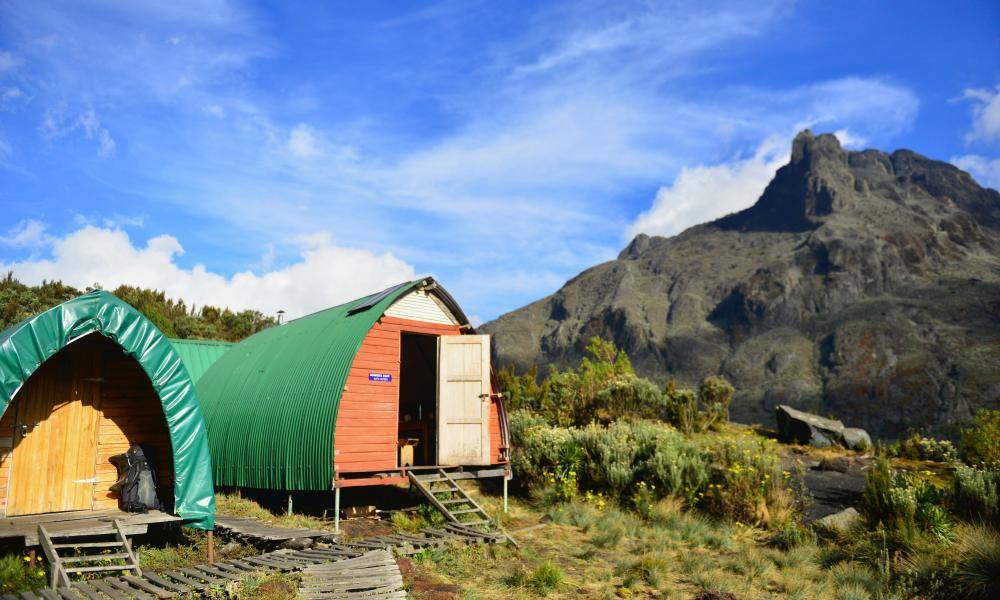 Climbers sleep in static tents or wooden huts, spacious enough for bunkbeds