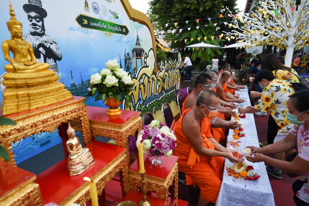 People queue to pour water on a Buddhist statue as they celebrate Songkran at Wat Pho temple in Bangkok, Thailand.