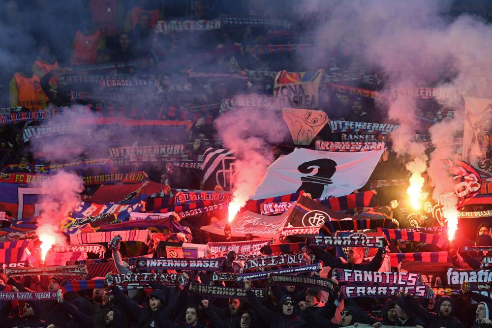 Flares are held aloft by Basel fans.