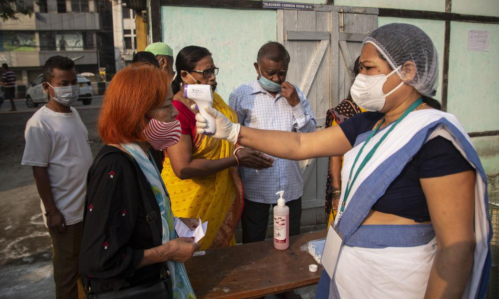 A health worker checks the temperature of voters at a polling station in Gauhati, India.
