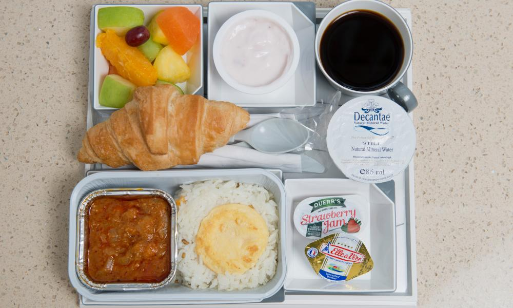 Plastic tray filled with plastic pots containing an airline meal from Malaysia Airlines.