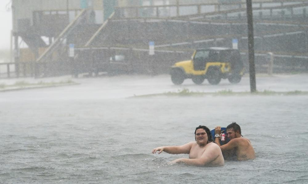 People play in a flooded parking lot Pensacola Beach, Florida.
