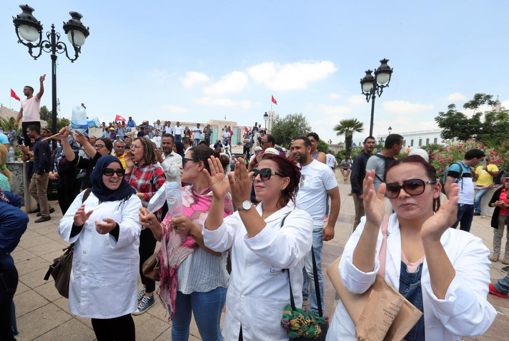 Public sector workers shout slogans in a protest demanding better work conditions next to the government palace in Tunis.