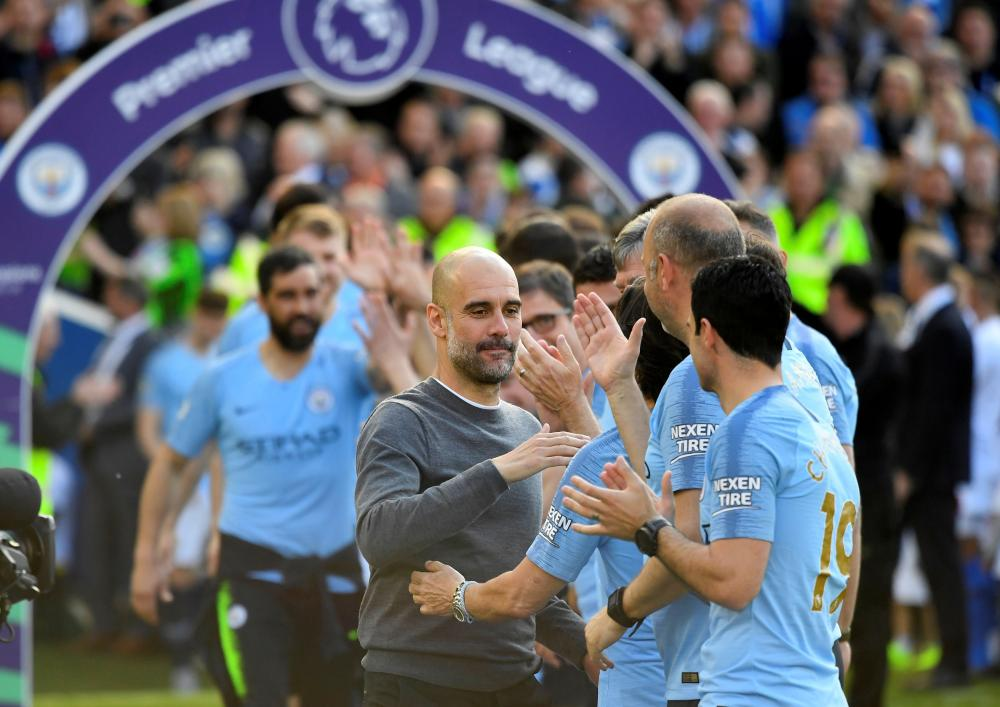 Guardiola leads out his players.