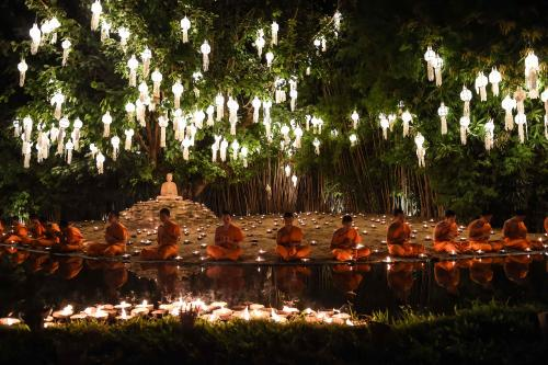Novice Buddhist monks sit to pray at Wat Phan Tao temple in Chiang Mai, Thailand, to mark the beginning of the annual Yi Peng festival