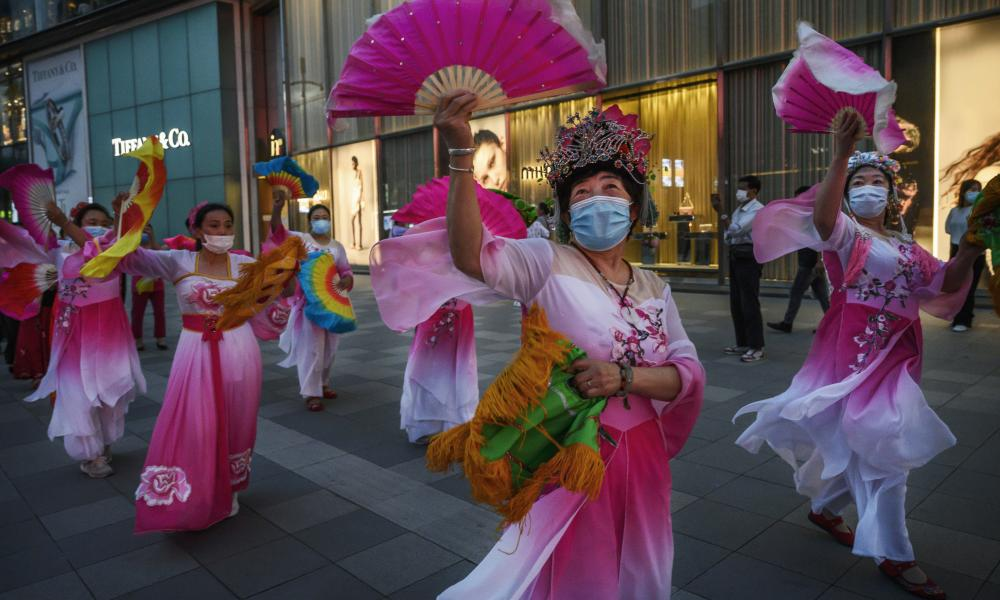 Chinese women wear protective masks and costume as they dance for exercise outside a luxury shopping mall on 4 June 2020 in Beijing.