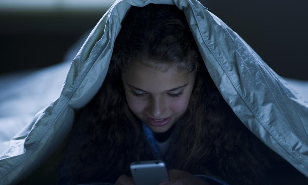 Girl under blankets at night with a smart phone