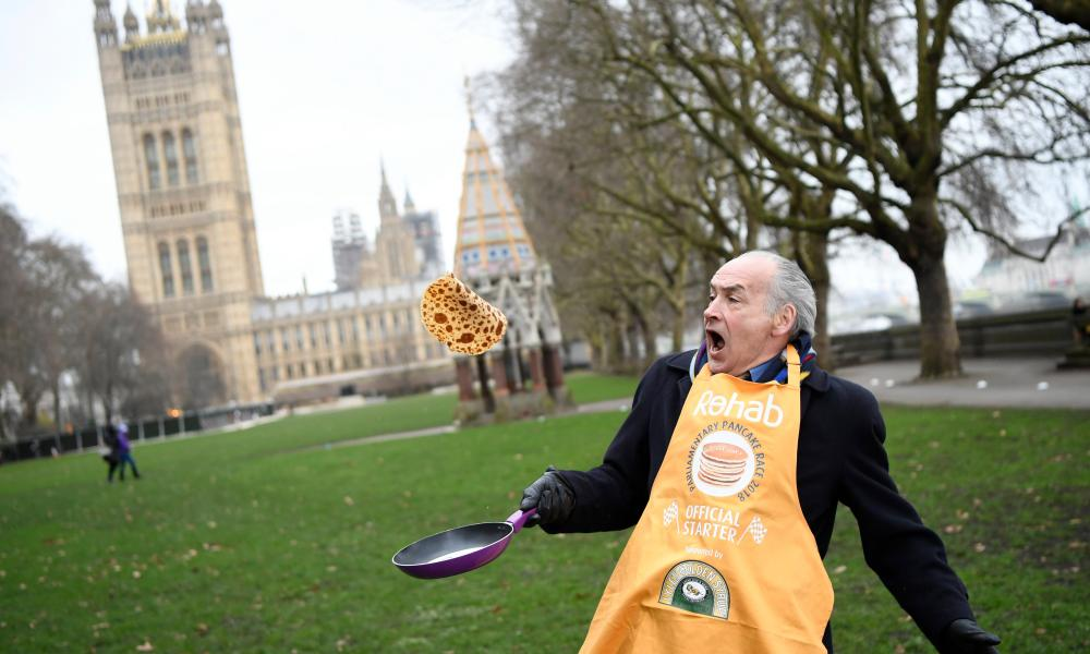 Television journalist Alastair Stewart poses before the annual Parliamentary Pancake Race in Westminster in London.