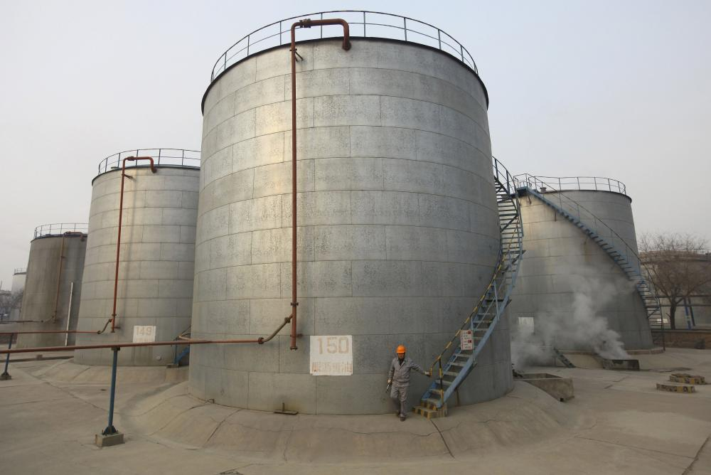 File picture of an employee walking down the stairs of an oil storage tank after a regular check at a PetroChina refinery in Lanzhou, Gansu province