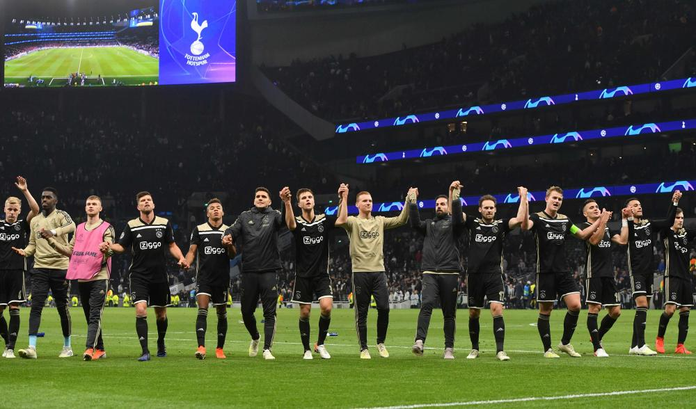 Ajax's players come over to celebrate with their supporters after their victory.