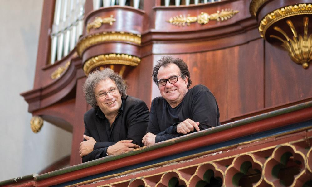 thierry escaich and richard galliano leaning over the balustrade of an organ loft and smiling