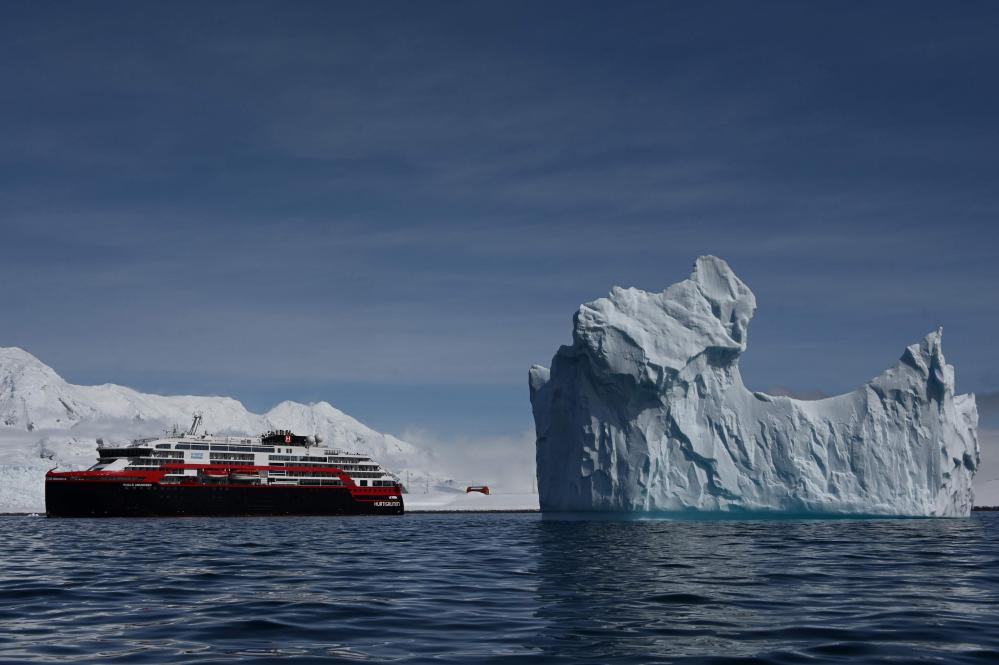 An iceberg and the Hurtigruten hybrid expedition cruise ship MS Roald Amundsen on Half Moon island.