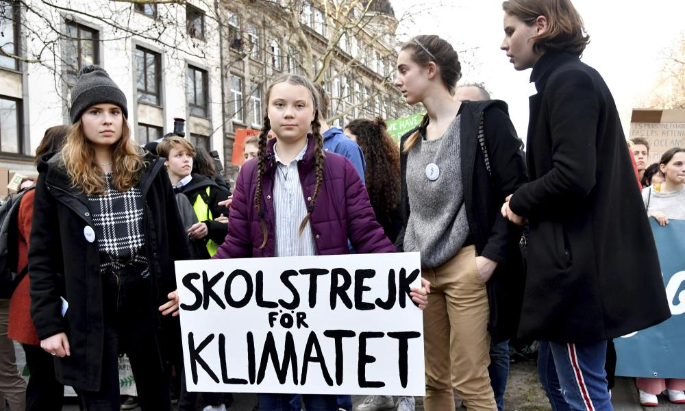 Swedish climate activist Greta Thunberg, center, holds a sign which reads: 'school strike for the climate' during a climate march in Brussels.