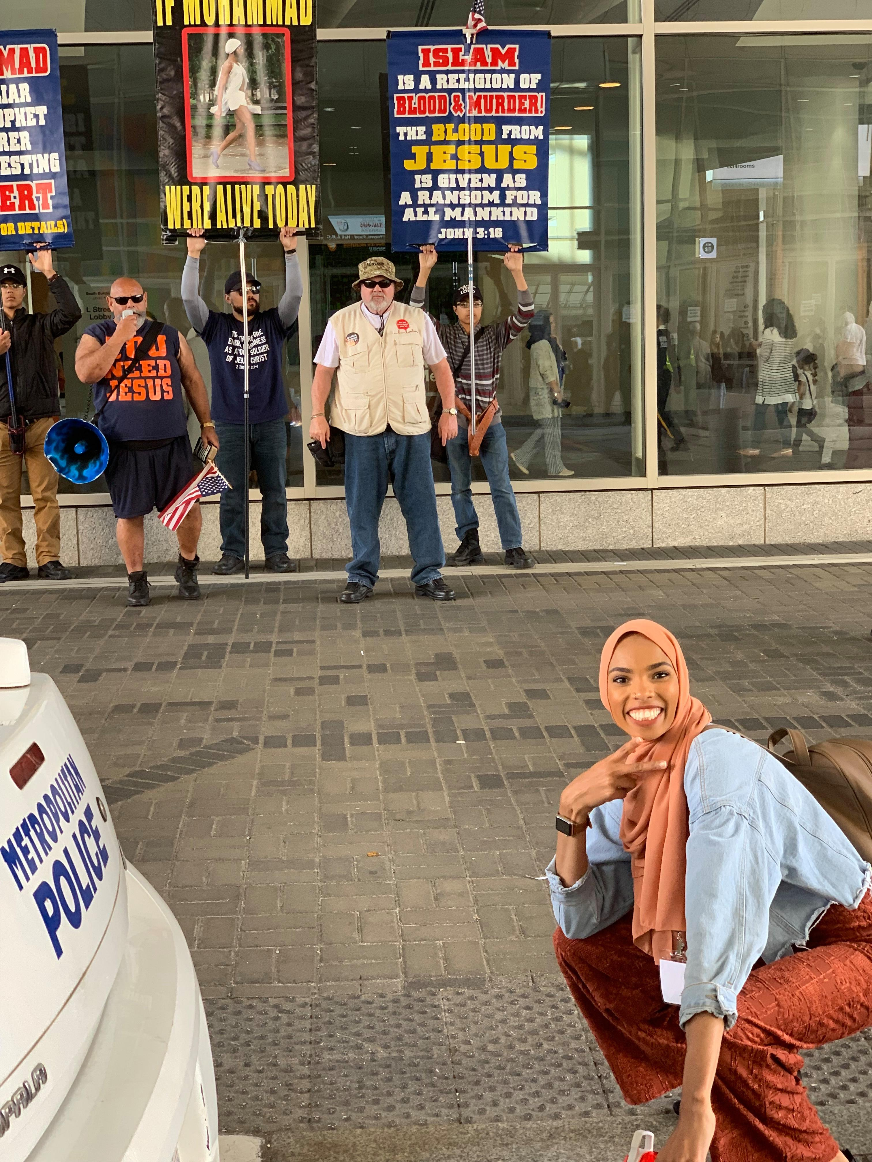 'Love in the face of bigotry': woman takes smiling stand against Islamophobic protesters