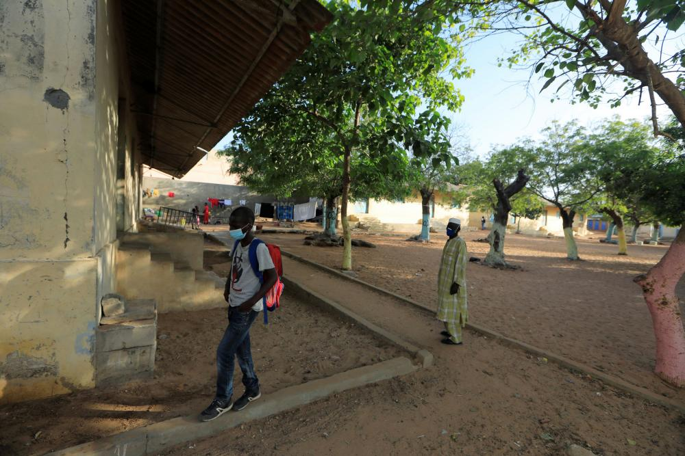 A schoolboy walks out of school after Senegal postponed the reopening of schools.
