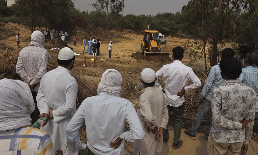 People in New Delhi, India, watch a burial ceremony from afar on 5 June.