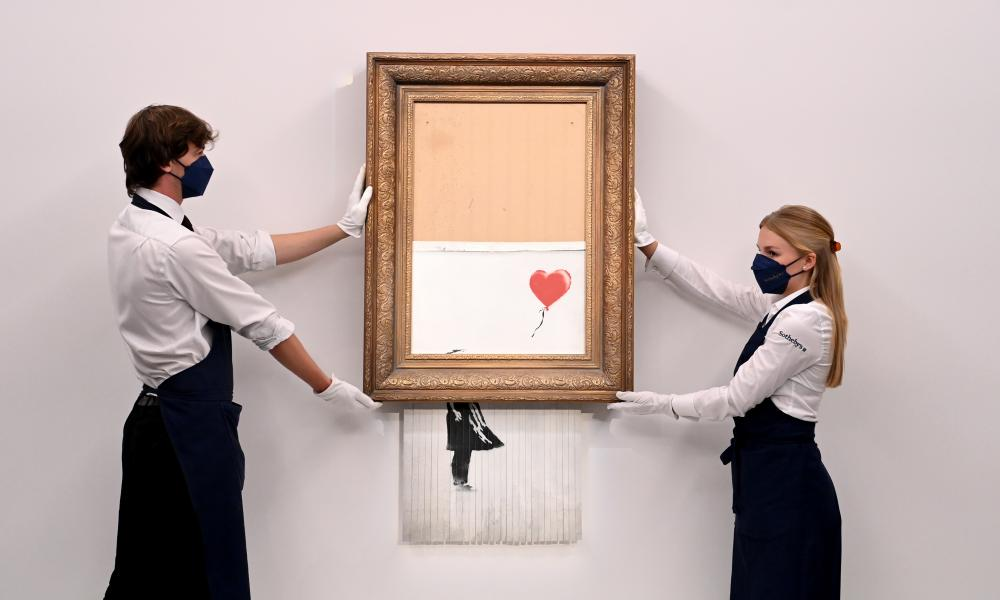 Gallery employees pose with Love is in the Bin by Banksy
