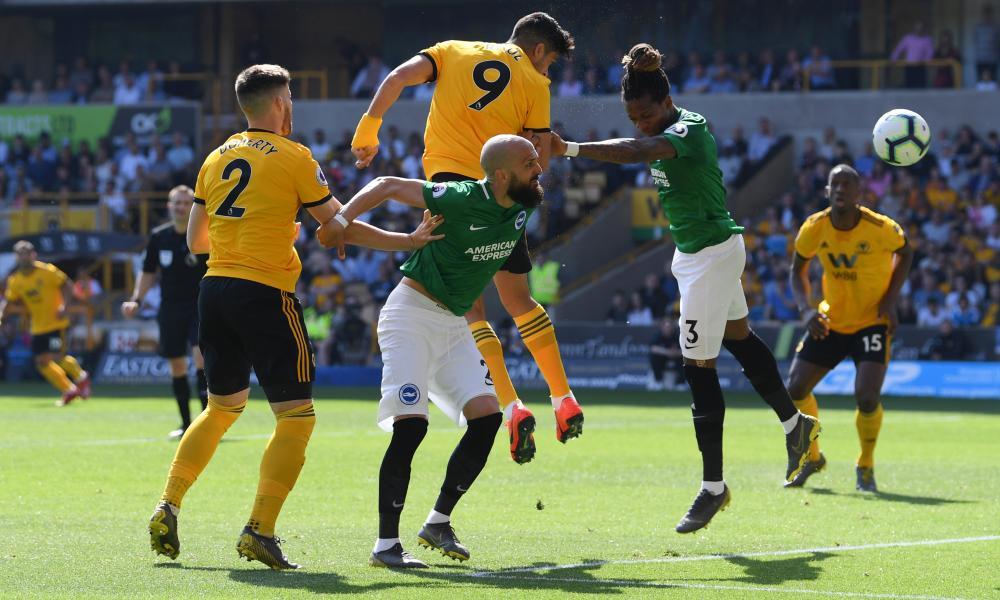 Raul Jimenez of Wolverhampton Wanderers heads wide under pressure from Gaetan Bong of Brighton.