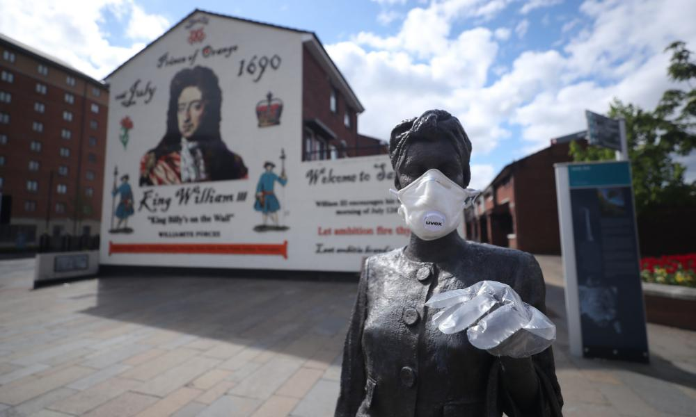 A statue by artist Ross Wilson entitled Mother Daughter Sister in Belfast is adorned with a mask and disposable gloves
