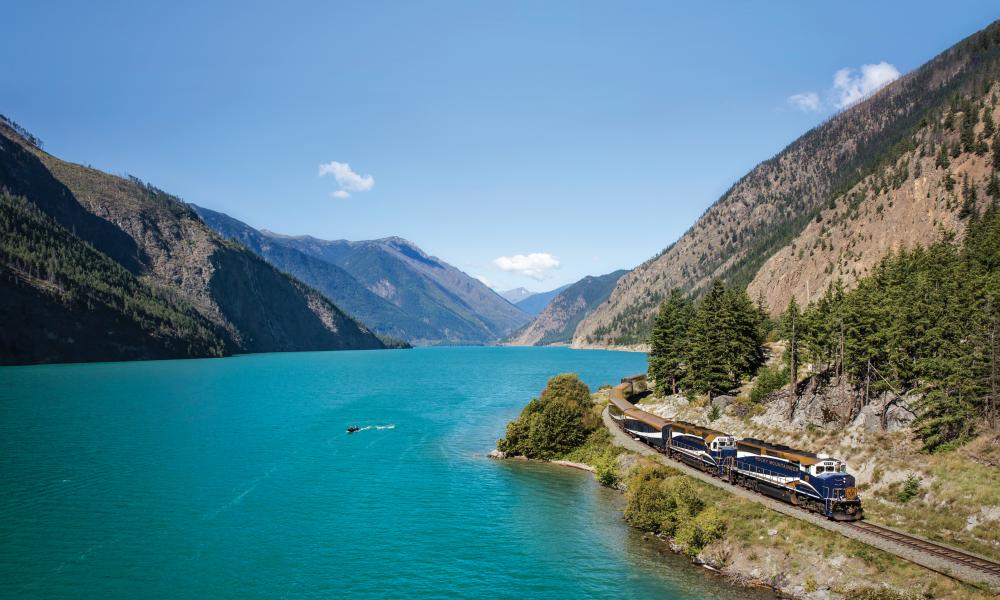 The train on tracks alongside the turquoise blue Seton Lake, mountains in the background.