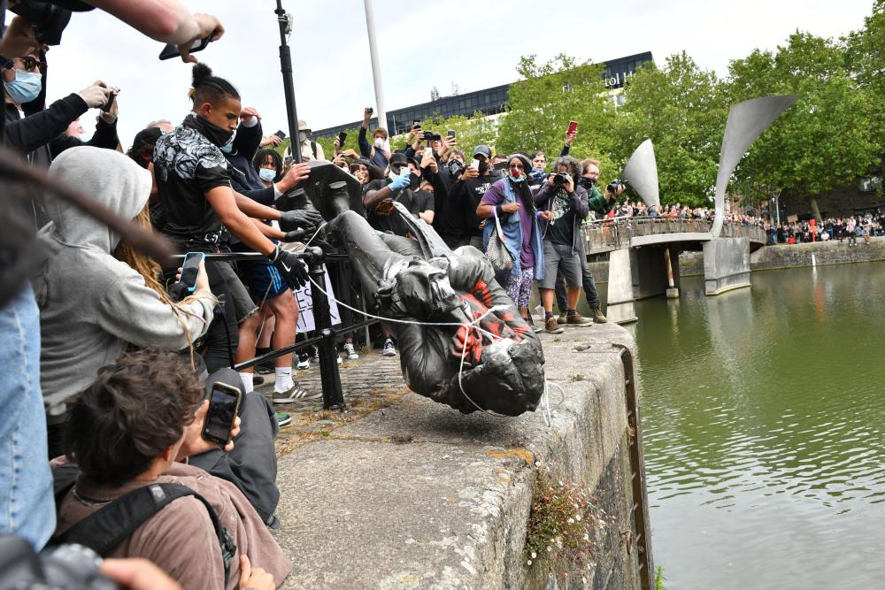 Protesters throw a statue of Edward Colston into Bristol harbour