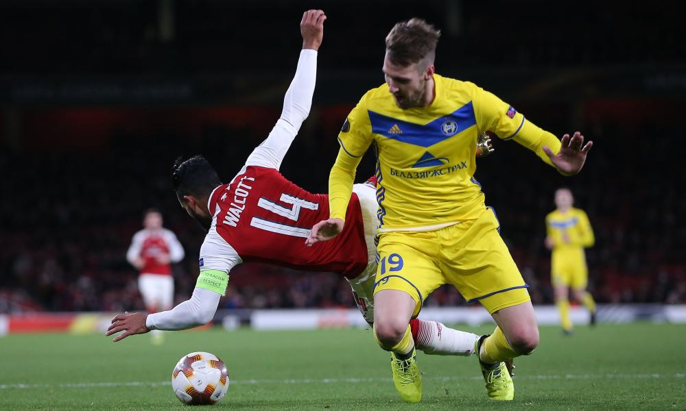 Theo Walcott goes to ground after being barged by Nemanja Milunovic of Bate Borisov and the referee points to the penalty spot.
