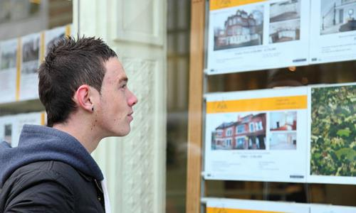 A first time buyer viewing houses in an estate agents window.
