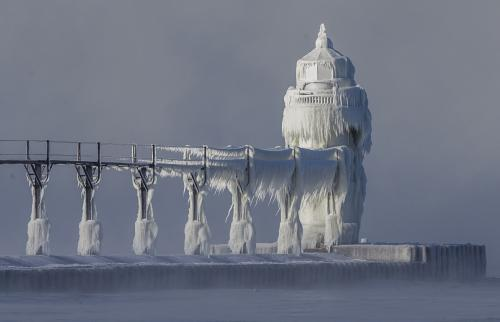 Extreme cold conditions cause ice accretions to cover the St. Joseph lighthouse and pier, on the southeastern shoreline of Lake Michigan, US