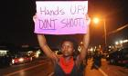 Protestors hold signs during a protest on West Florissant Road in Ferguson, Missouri.