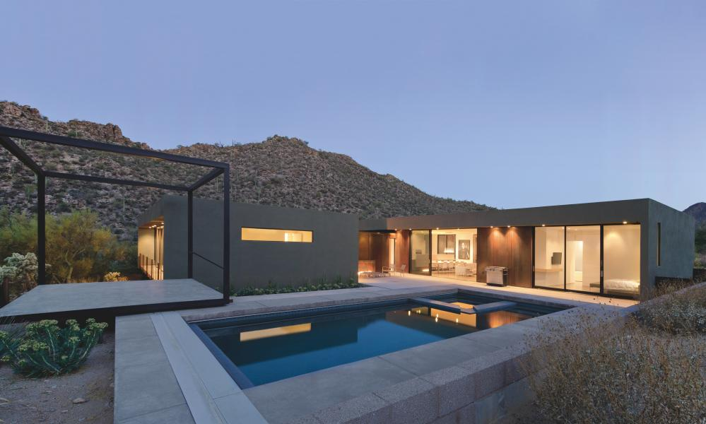 Lit low-level building with pool, deck and freestanding black framework