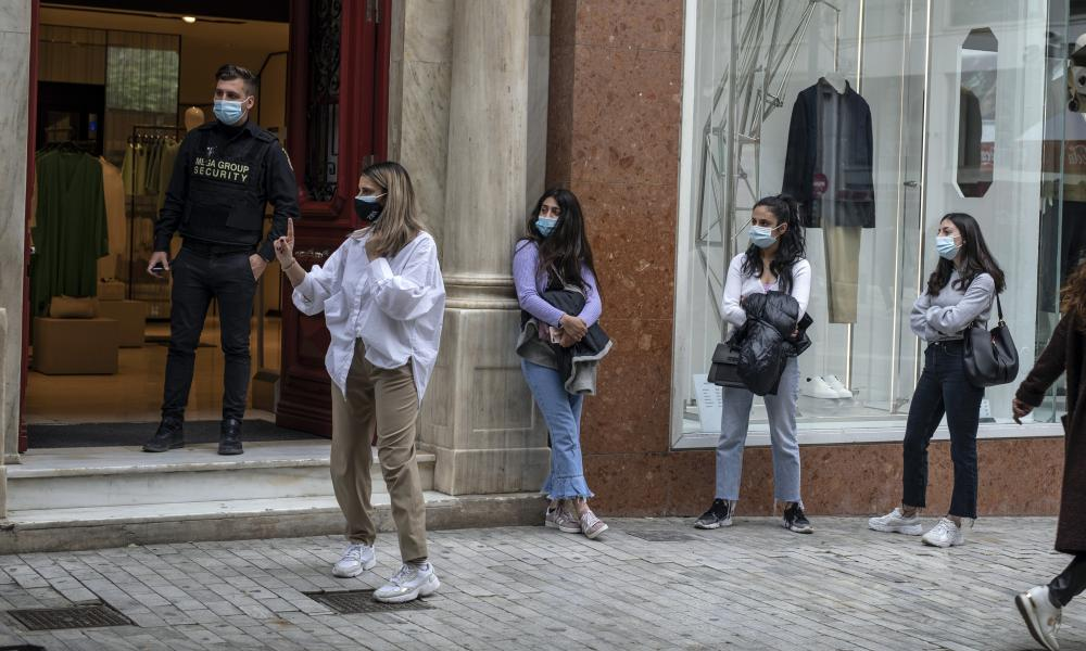 Customers wearing protective face masks queue outside a clothing store in Ermou street, central Athens, on Monday, April 5, 2021.