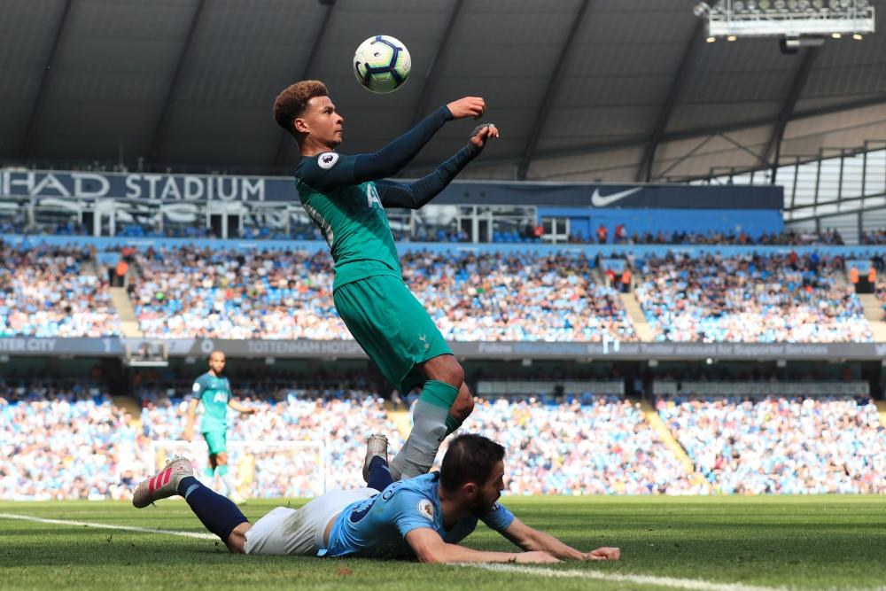 Dele Alli of Tottenham Hotspur controls the ball after battling for possession with Bernardo Silva of Manchester City.